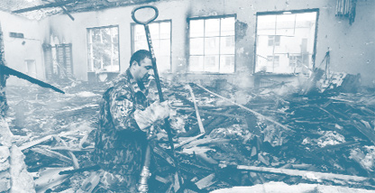 A soldier picks his way through rubble in Beslan