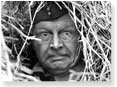 Corporal Jones pokes his face out from inside a haystack.