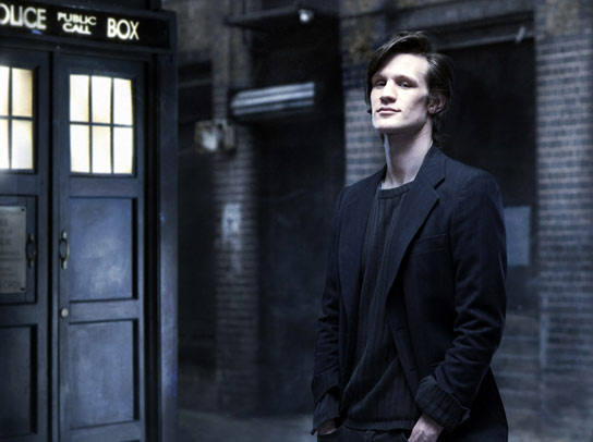 Matt Smith is the Doctor, pictured down an alleyway, his TARDIS policebox is behind him.