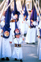 Adults and children dressed in bright blue hoods at a Spanish Holy Week festival