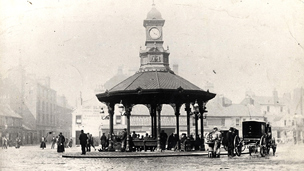 Black and white view of the Bridgeton Cross Shelter, an octagonal shelter supported on slim columns with a short clock tower above.