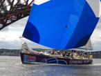 Edinburgh Inspiring Capital and crew passing under the Forth Rail Bridge, flying saltire spinnaker