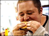Homem comendo hamburguer