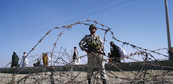 A soldier of Pakistan's paramilitary force, behind barbed wire, at the Afghanistan border. Photo credit: AP